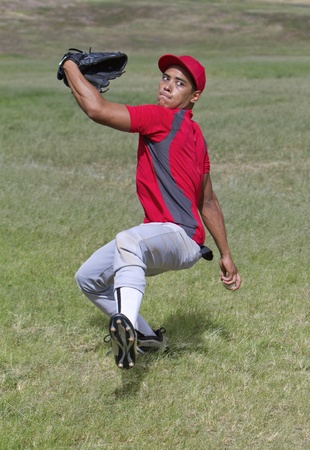 Baseball player winds up for a big pitch photo