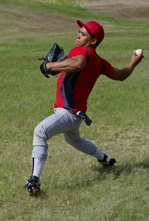 Baseball player throws a ball with strength photo