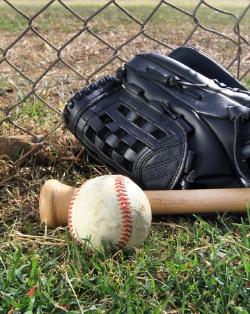 A baseball bat, glove, and ball lay in a field against a chain link fence