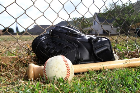 Baseball glove, bat, and ball lay in a field
