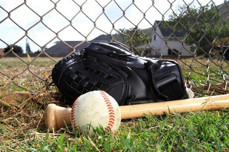 Baseball glove, bat, and ball lay in a field