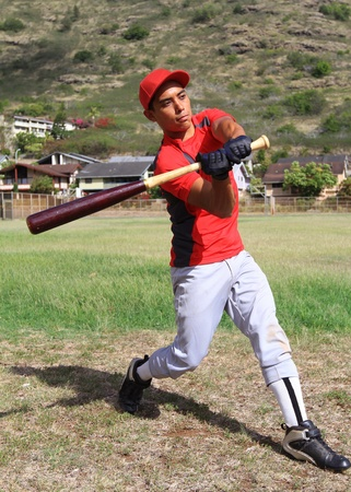 Baseball batter mid-swing in an open grassy field Stock Photo