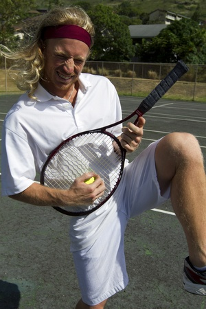 A blonde male tennis player goofs around with his tennis racquet
