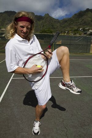A blonde male tennis player goofs around with his tennis racquet on the court