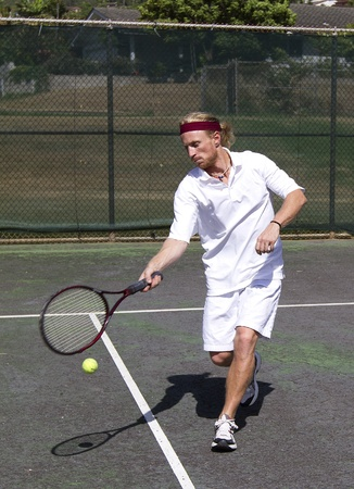 Male tennis player takes a forehand swing at the ball Stock Photo