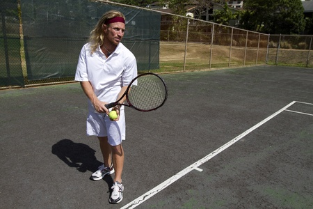 A blonde male tennis player gets prepared to make a strong overhand serve over the net