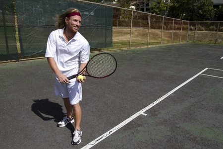 A smiling blonde male tennis player is ready to make a strong serve