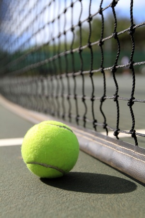 A tennis ball lies on the court next to the net in the daytime