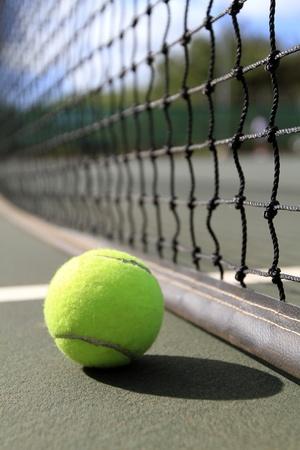 tenis: Una pelota de tenis se encuentra en la cancha junto a la red durante el día