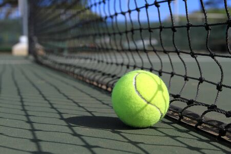 A tennis ball lies on the court next to the net in broad sunny daylight