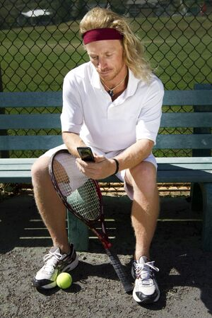 A blonde male tennis player takes a break from the game to check his cell phone