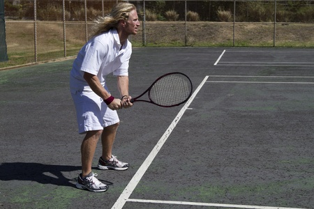 A blonde male tennis player concentrates as he prepares to return the serve