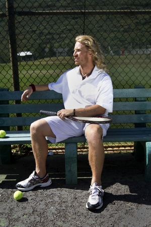 A handsome blonde tennis player sits on the bench on the sidelines