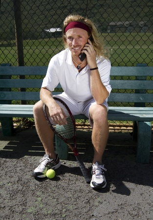 A handsome blonde tennis player sits on the sideline bench and talks on his cell phone Stock Photo