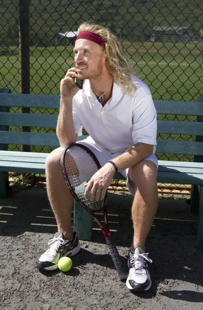 A handsome blonde tennis player sits on the sideline bench and chats on his cell phone