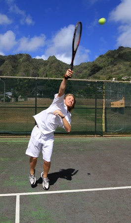 A handsome blonde tennis player serves the ball over the net with confidence