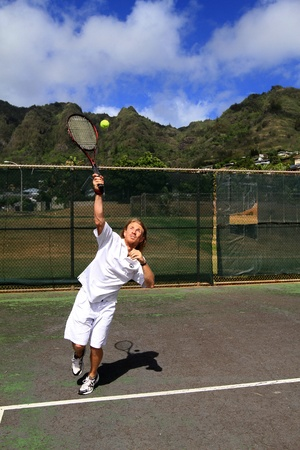 A handsome blonde tennis player makes a solid serve over the net