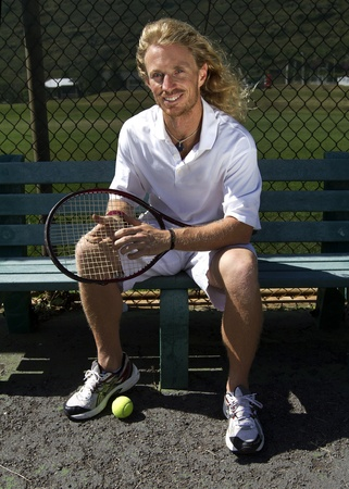 A handsome blonde tennis player sits on the bench on the sidelines and smiles