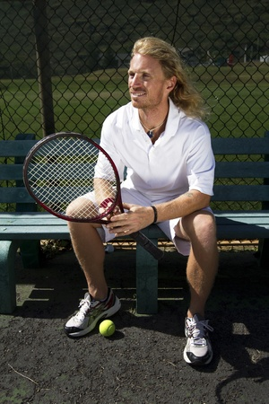 A handsome blonde tennis player watches the court from the sidelines Stock Photo