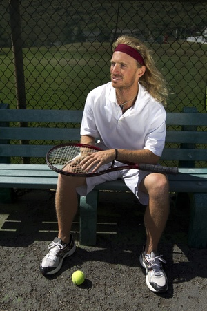 A blonde male tennis player waits his turn on the sideline bench Stock Photo