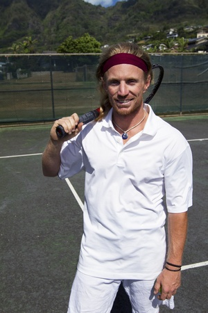 A handsome blonde tennis player poses with his racquet on the court