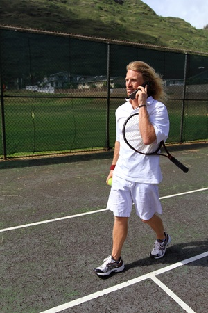 A handsome blonde tennis player talking on his cell phone on the court. Stock Photo