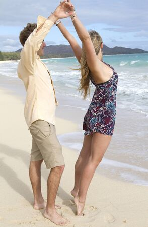 A beautiful young couple have fun and dance on the beach
