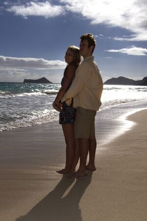 A beautiful young couple embrace on the shore of a beach in Hawaii Stock Photo