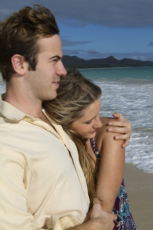 Young couple embrace on the beach in Hawaii Stock Photo