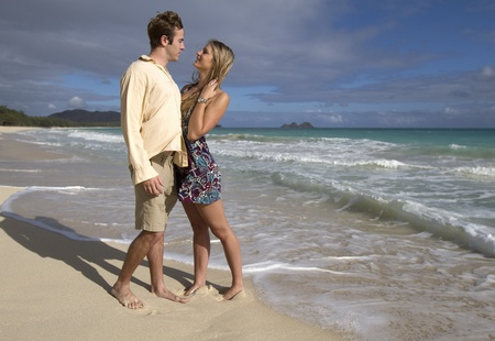 A beautiful young couple gaze into each others eyes on the beach in Hawaii Stock Photo