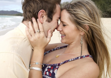 A beautiful young couple get intimate on the beach in Hawaii Stock Photo
