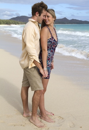 A beautiful young couple embrace on the shore in Hawaii Stock Photo