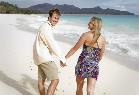 A beautiful young couple walks on the beach in Hawaii