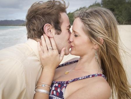 young couple kiss: Un beso hermosa joven pareja en la playa en Hawai Foto de archivo