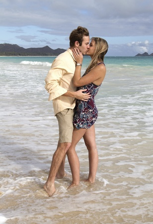A beautiful young couple kiss on the shore in Hawaii Stock Photo