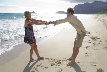 A beautiful young couple play around on the beach in Hawaii Stock Photo