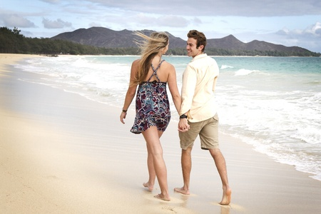 A beautiful young couple go for a walk on the beach in Hawaii Stock Photo