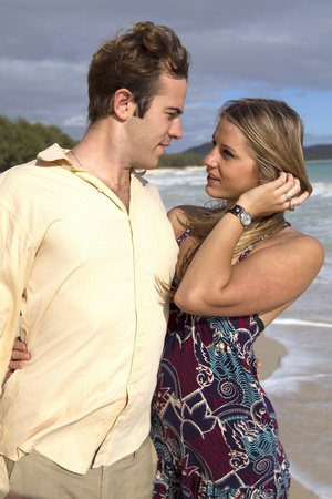 A beautiful young couple stare into each others eyes on the beach in Hawaii