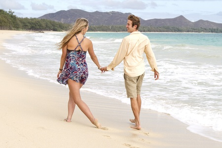 A young couple stroll down the beach playfully.