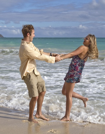 A beautiful young couple swing in each others arms on the beach in Hawaii
