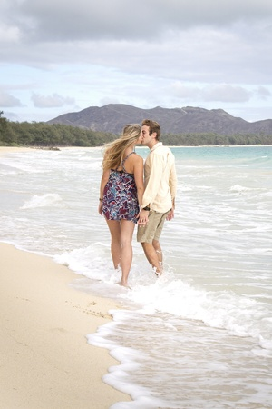 A beautiful young couple walk on the beach and kiss in Hawaii