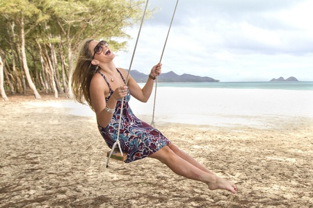 A beautiful girl swings and laughs on a beach in Hawaii