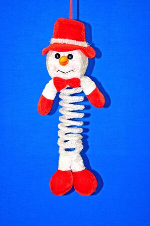Snowman ornament with a springy body and fleece hat and bowtie.