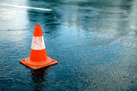 Traffic cone in the road on a rainy day