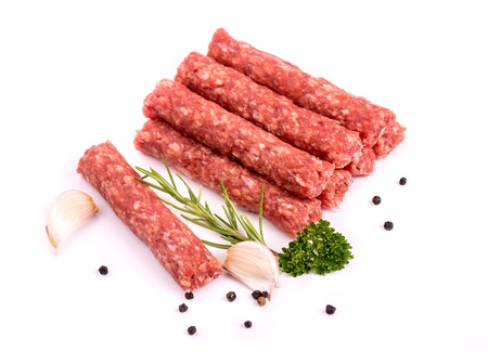 bosnia: Cevapcici - ready for the grill Delicious meat cevapcici with pepper, rosemary, parsley and garlic, isolated on white Stock Photo