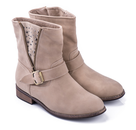 An elegant pair of woman s beige boots on a white background
