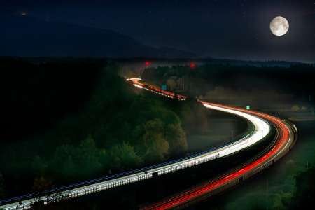Long Exposure of Car Lights on Motorway Car Lights on Motorway with Moon, stars and green forrest