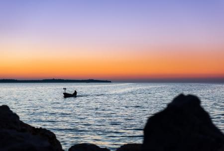 Halász jön haza kishajó hazatér, miután este halászati Téli délben Stock fotó