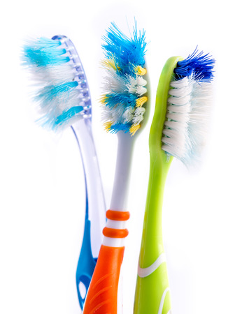 Old used colorful toothbrushes isolated on white background Imagens