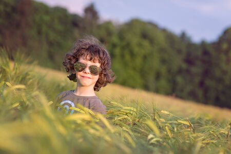 Boy playing on the filed in sunset, sunglasses Stock Photo